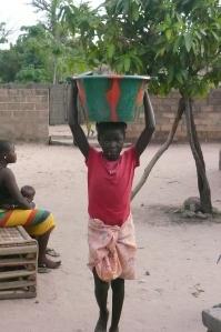 Mit Leichtigkeit trägt das Mädchen einen vollen Eimer auf dem Kopf. Fließendes Wasser gibt es nicht auf dem Hof.